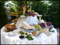 Rustic platters table with imported cheese wheels and antipasto platters at a Tuscan style backyard wedding