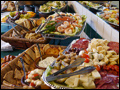 appetizer party featuring trays of hummus and pita breads, antipasto and veggie platters, shrimp cocktail and fruit platters
